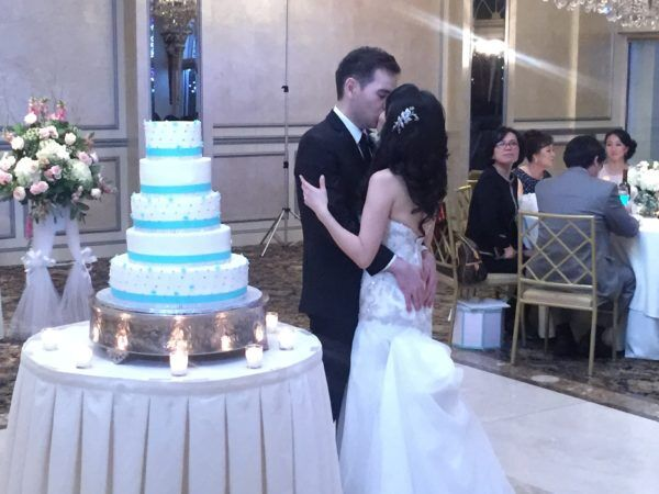 Bride and Groom share a kiss by the wedding cake at the Surf club in New Rochelle NY