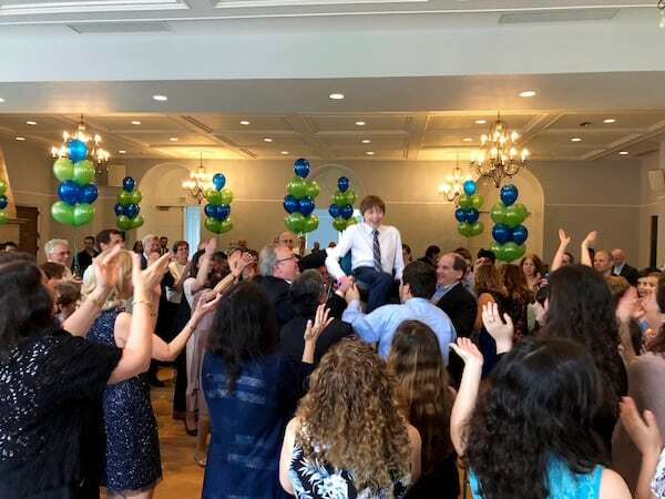 Bar Mitzvah boy lifted on chair during Hora