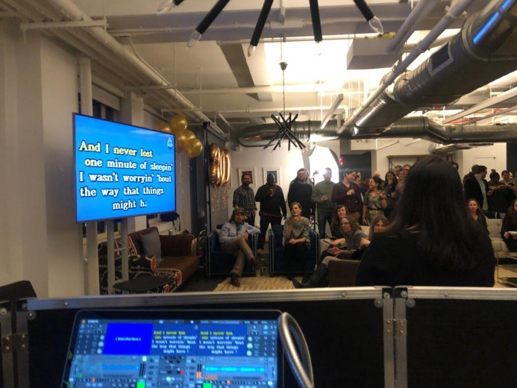 employees sing karaoke of large screen tv from expressway music nyc