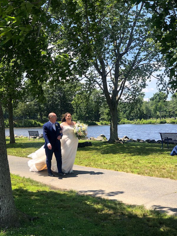 Father walking Bride down aisle by Lake to be married